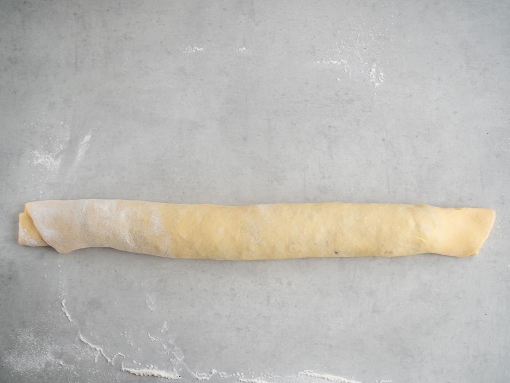 na blacie zwinięte ciasto drożdżowe w rulon