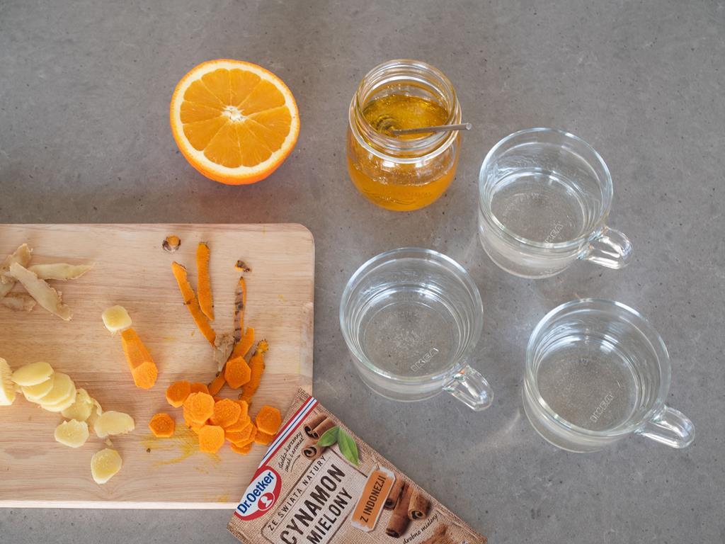 na blacie pokrojony imbir i kurkuma, szklanki z wodą