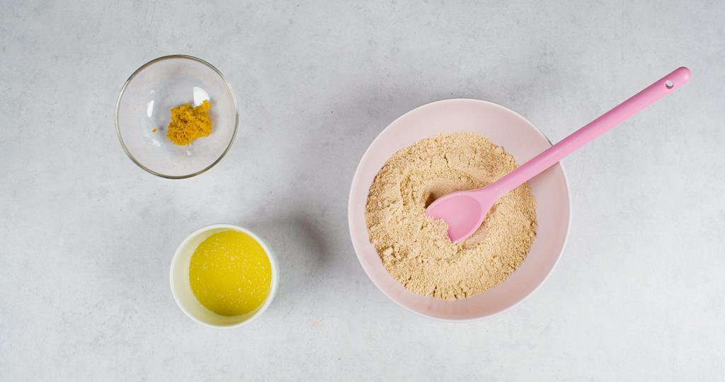 Pokruszone ciasteczka, masło w miseczce i skórka z pomarańczy
