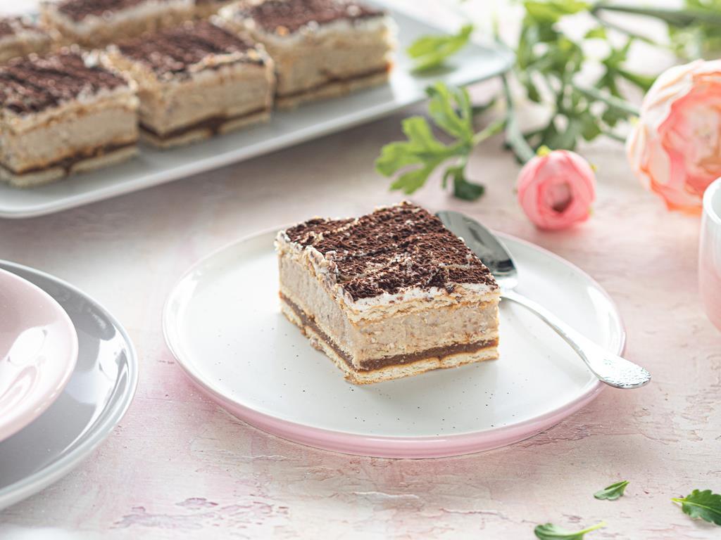 Ciasto a'la 3 bit wegańskie z budyniem z kaszy jaglanej i karmelem z daktyli posypane kakao, na biało-różowym talerzyku.