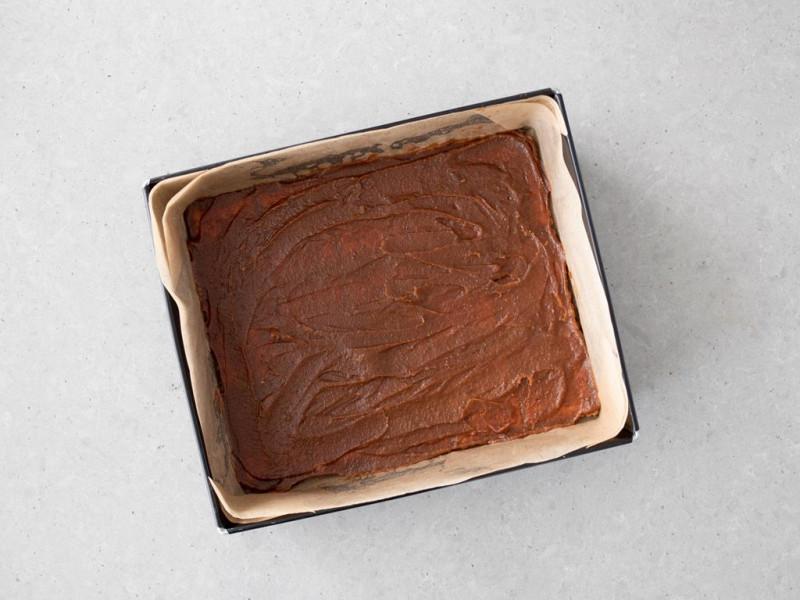 Wyłożona forma herbatnikami. Na herbatnikach rozsmarowany karmel z daktyli.