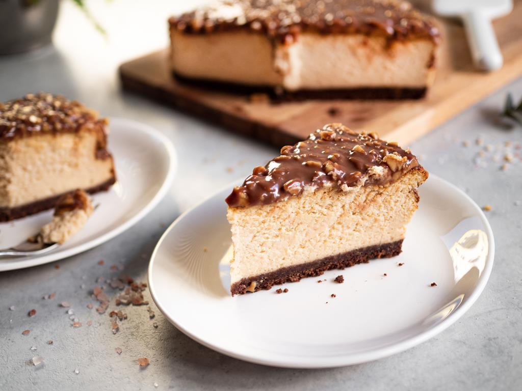 na białym talerzyku pieczony sernik snickers