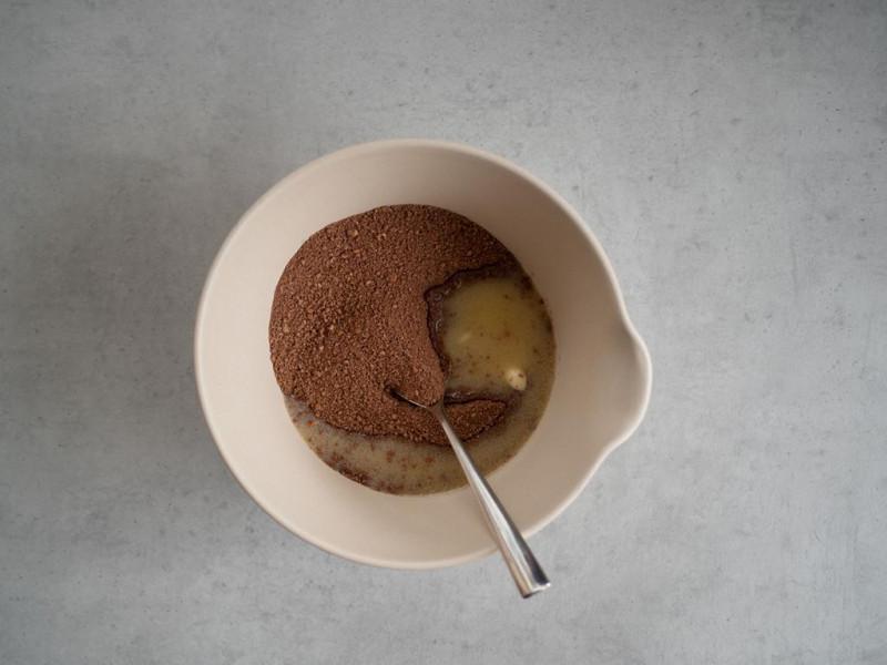 w misce na szarym blacie pokruszone herbatniki z kakao z roztopionym masłem
