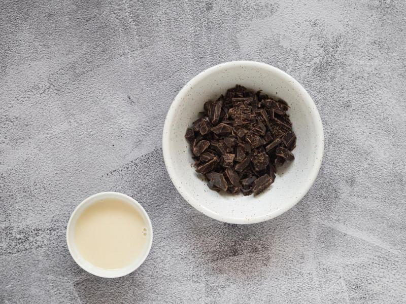 Połamana gorzka czekolada w miseczce, obok mleko sojowe.