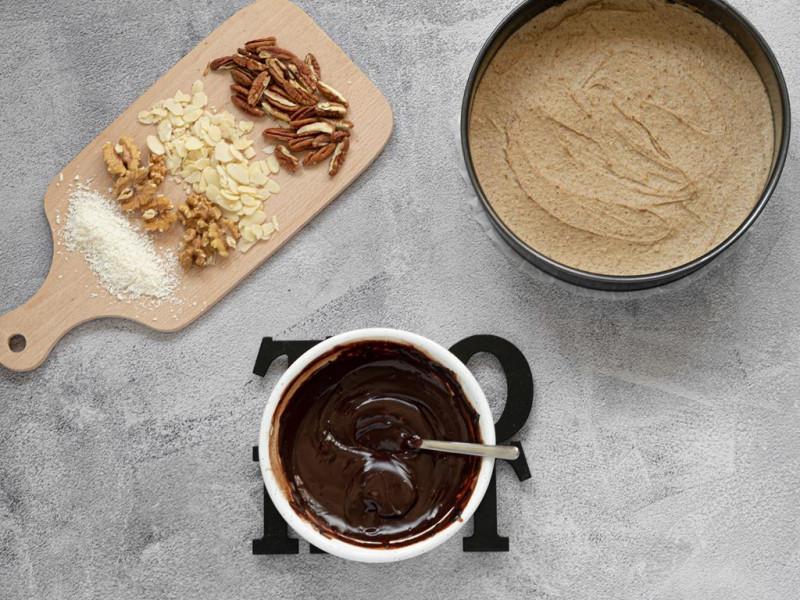 W miseczce polewa czekoladowa, obok tortownica z ciastem i na desce bakalie: orzechy pekan, migdały w płatkach, orzechy włoskie i wiórki kokosowe.