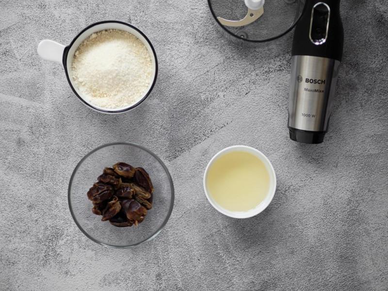 Daktyle, mąka kokosowa i olej kokosowy w miseczce. Obok blender MaxoMixx firmy Bosch.