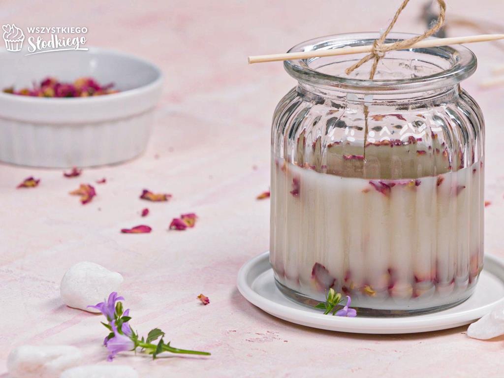 na stole ręcznie robiona świeczka z wanilią i płatkami róż