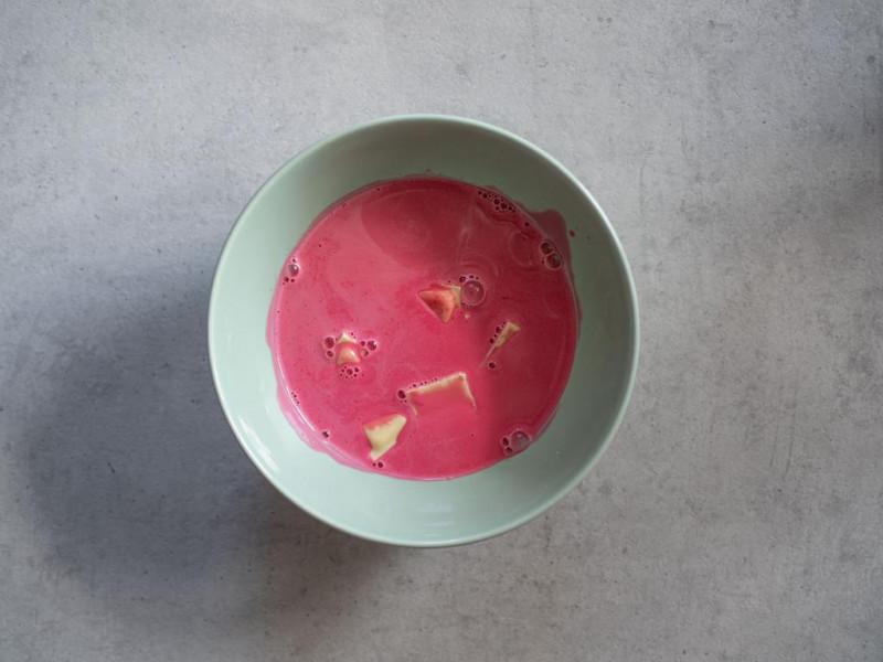 w miseczce biała czekolada zalana zabarwioną śmietanką na różowo