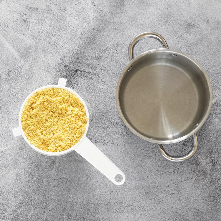 Przepłukana kasza jaglana na sitku. Obok garnek z wodą.