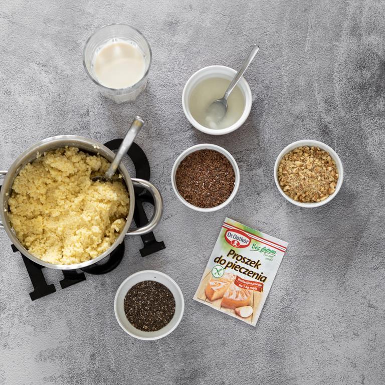 Ugotowana kasza jaglana, obok w miseczkach, posiekane orzechy włoskie, siemię lniane, nasiona chia, rozpuszczony olej kokosowy i napój sojowy oraz proszek do pieczenia.