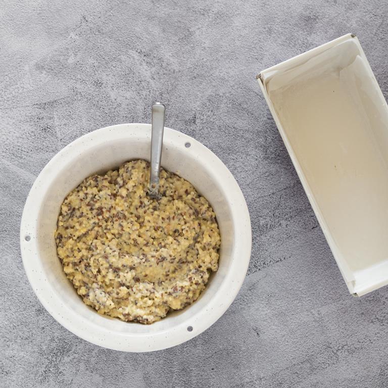 Wymieszana masa na chleb z kaszy jaglanej. Obok foremka wyłożona papierem do pieczenia.
