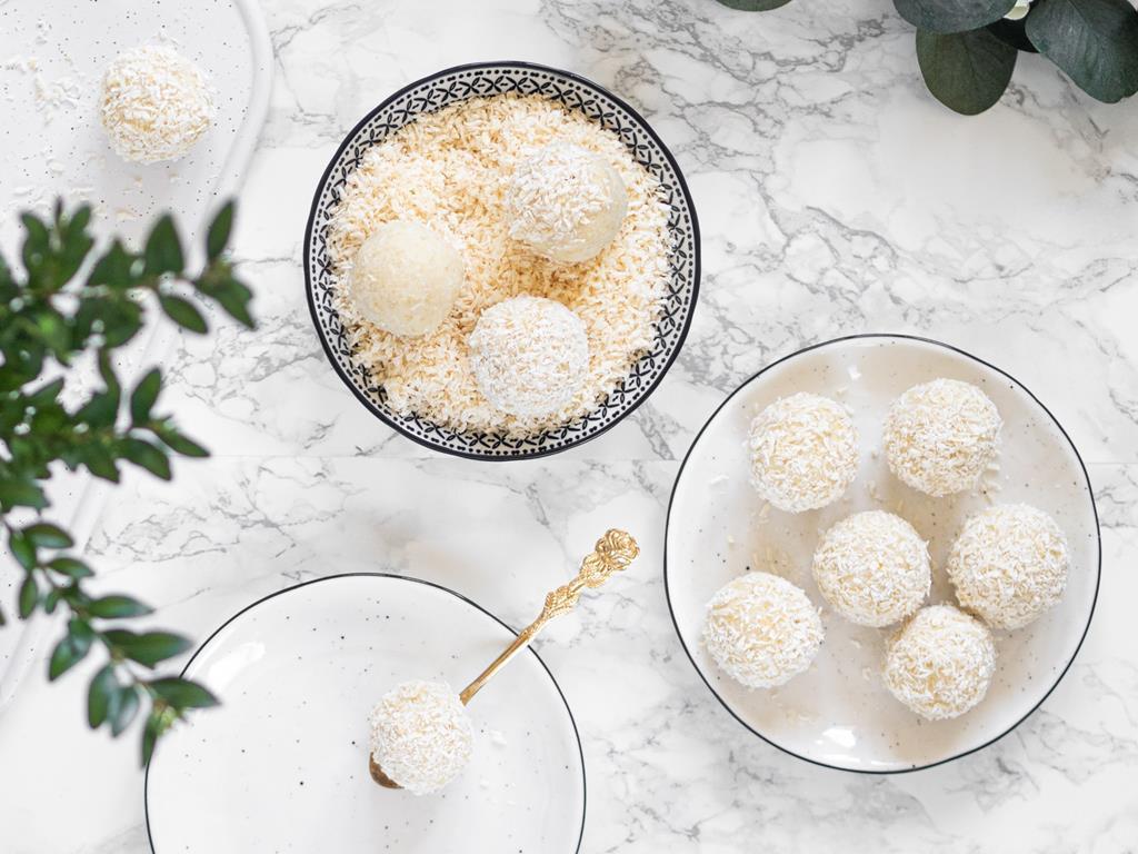 Jaglane kulki mocy kokosowe obtoczone w wiórkach kokosowych. Na talerzyku jedna kulka kokosowa na złotej łyżeczce. Część kulek do obtoczenia w misce z wiórkami kokosowymi.