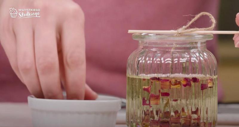 Świeczka waniliowa z płatkami róż w szklanym naczyniu