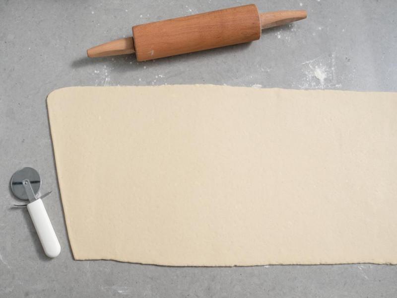 rozwałkowanie ciasta na croissanty na długi prostokąt i wycinanie z niego trójkątów