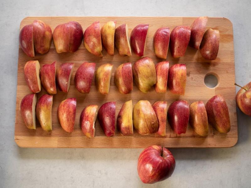 na drewnianej desce pokrojone ćwiartki czerwonych jabłek