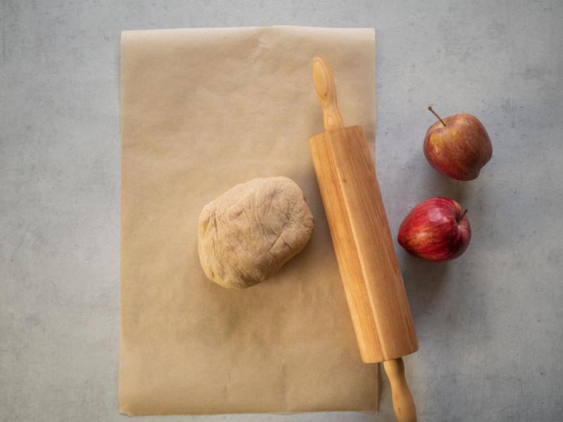 na blacie papier do pieczenia z kulką ciasta, wałek oraz jabłka