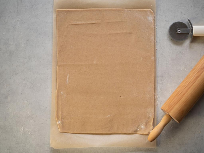 na papierze do pieczenia rozwałkowane kruche ciasto na kształt prostokąta