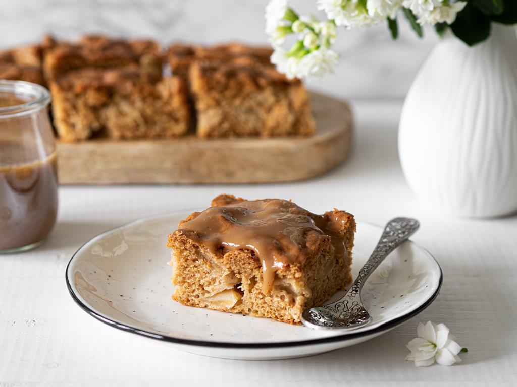 wegański placek z jabłkami i sosem cynamonowym na białym talerzyku w kropki. Obok w słoiczku sos cynamonowy, kawałki ciasta na desce i biały wazon z kwiatami.
