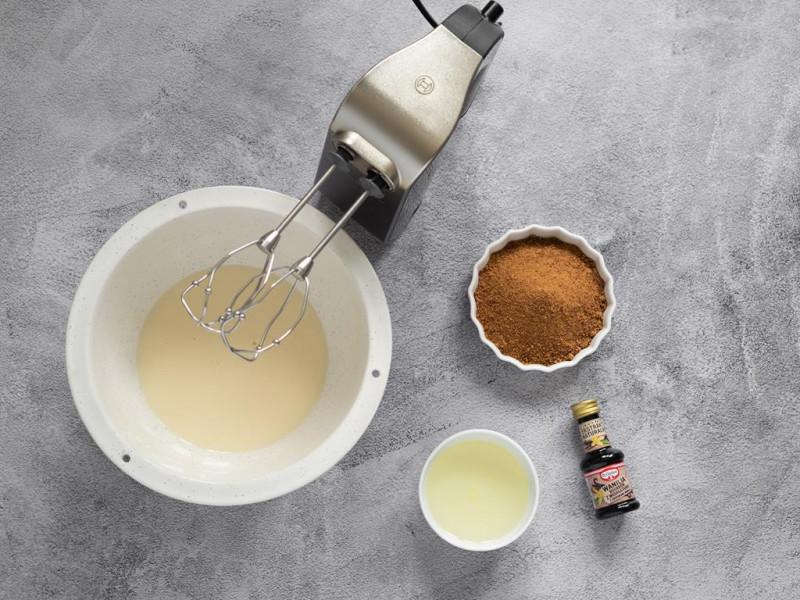 Mikser ręczny firmy bosch, w misce napój sojowy. Obok cukier kokosowy, ekstrakt z wanilii Dr. Oetker i olej rzepakowy.