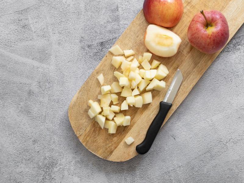Pokrojone w kostkę jabłka na drewnianej desce.
