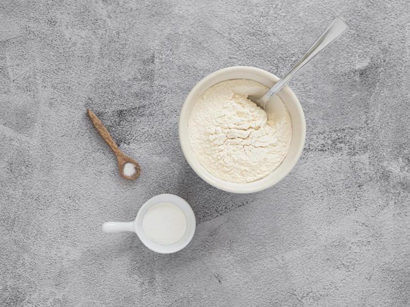 Mąka pszenna w misce, obok proszek do pieczenia i szczypta soli.