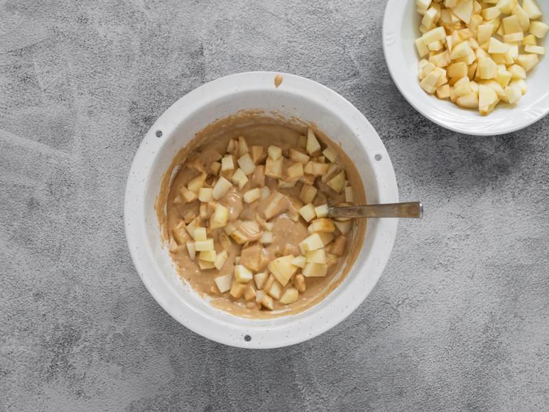 Pokrojone jabłka wymieszane z ciastem w dużej misce.