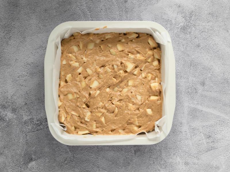 Ciasto na placek z jabłkami wyłożone do kwadratowej formy.