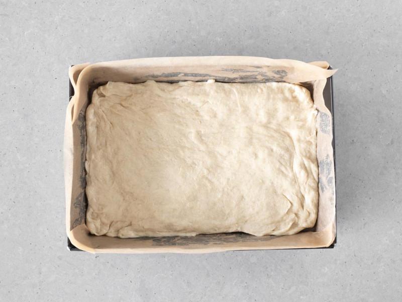 Wegańskie ciasto drożdżowe przełożone do formy.