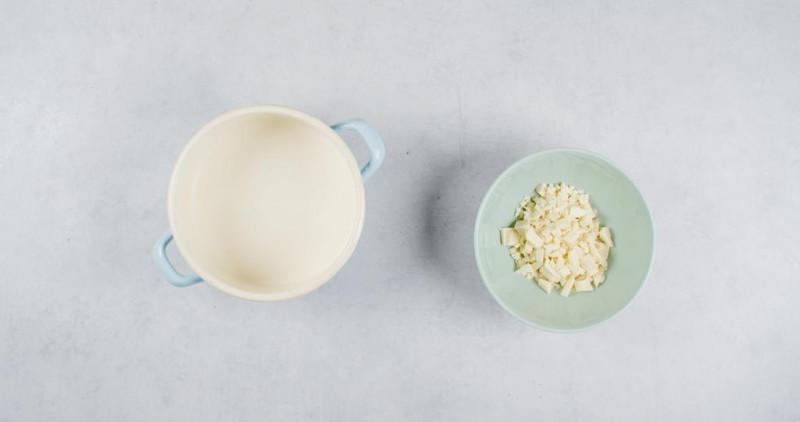 na blacie garnek z mlekiem obok miseczka z pokrojoną białą czekoladą
