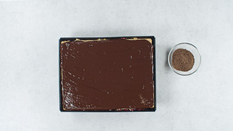 w prostokątnej blaszce ciasto z polewą czekoladową i miseczka z tartą czekoladą