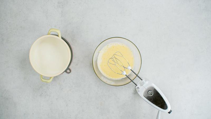 w misce krem budyniowy z mikserem obok garnek z mlekiem
