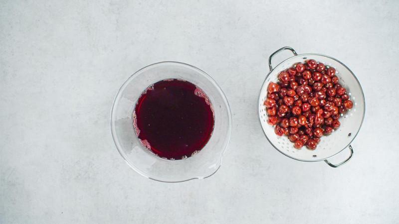 na blacie cedzak z drylowanymi wiśniami obok szklane naczynie z sokiem wiśniowym