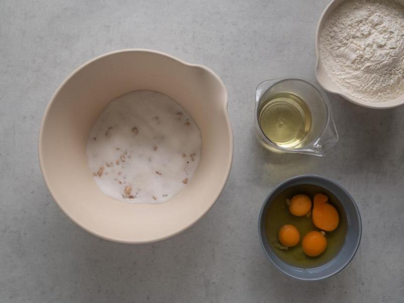 na blacie miska z drożdżami zasypanymi cukrem, miseczka z wybitymi jajkami, miarka z olejem oraz mąka psz