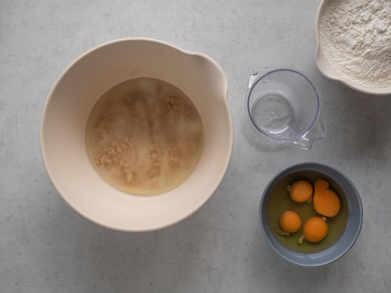 na blacie miska z drożdżami zasypanymi cukrem i zalane olejem, miseczka z wybitymi jajkami oraz mąka psz