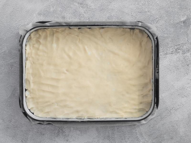 Wegańskie ciasto kruche rozłożone na blasze.