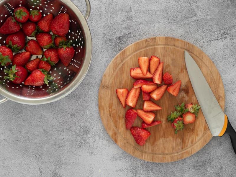 Umyte truskawki w durszlaku i pokrojone na drewnianej desce.
