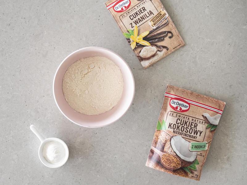 Cukier kokosowy i cukier z wanilią Dr. Oetkera na blacie, obok w miseczkach mąka pszenna wymieszana z solą i proszek do pieczenia.