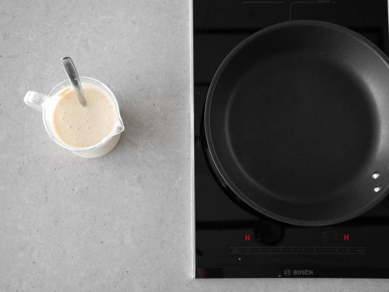 Patelnia na kuchence indukcyjnej firmy Bosch. Obok wymieszane ciasto na pancakes wegańskie.