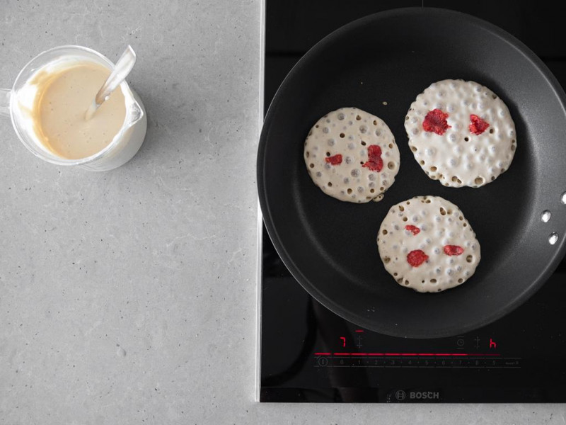 Ciasto na pancakes wegańskie i smażące się obok pancakes z malinami.