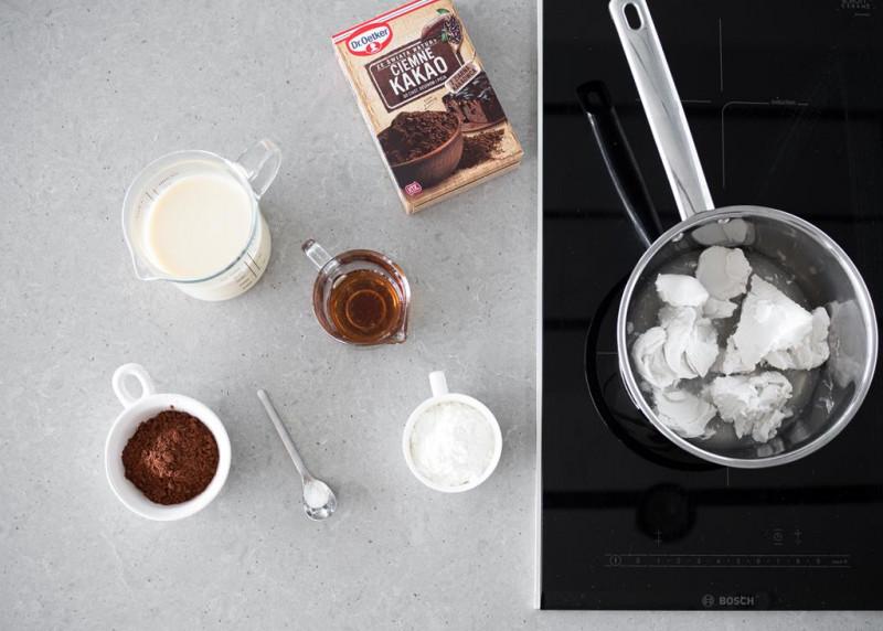 Mleko kokosowe w garnku na płycie indukcyjnej Bosch. Obok kakao ciemne Dr. Oetkera i w miseczkach napój sojowy, syrop klonowy, sól, skrobia kukurydziana i kakao.