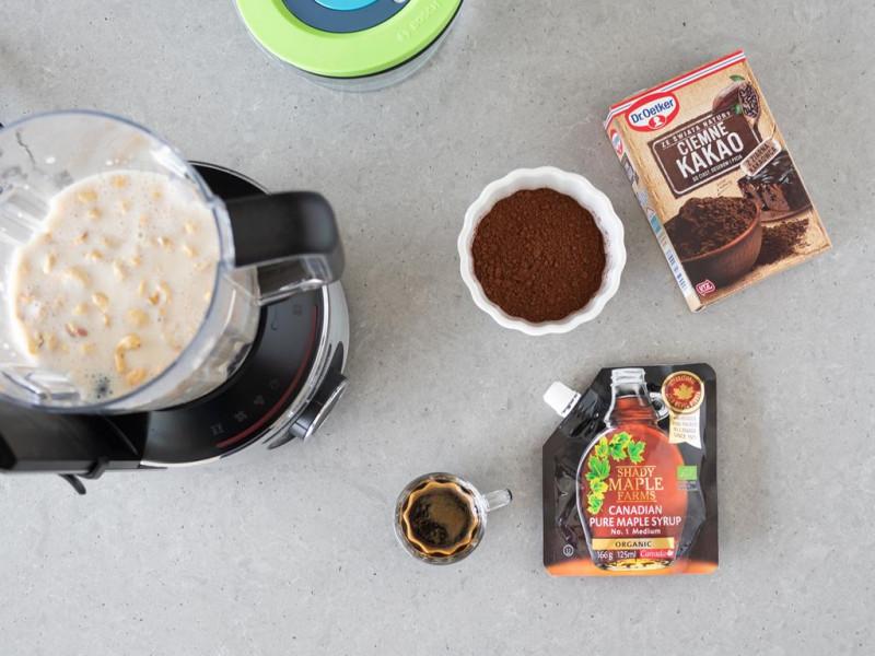 W blenderze kielichowym Bosch VitaMaxx napój sojowy z nerkowcami i daktylami. W miseczkach kakao Ciemne Dr. Oetkera, syrop klonowy i espresso.