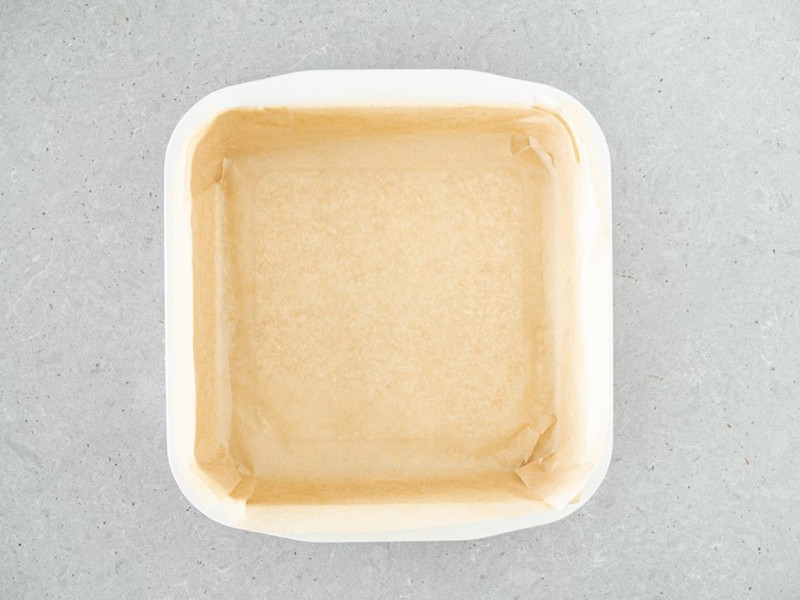 Kwadratowa foremka firmy Dr. Oetker wyłożona papierem do pieczenia.