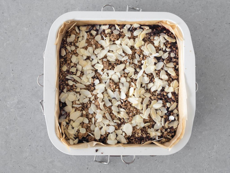 Upieczone ciasto owsiane z jagodami, posypane płatkami migdałów.
