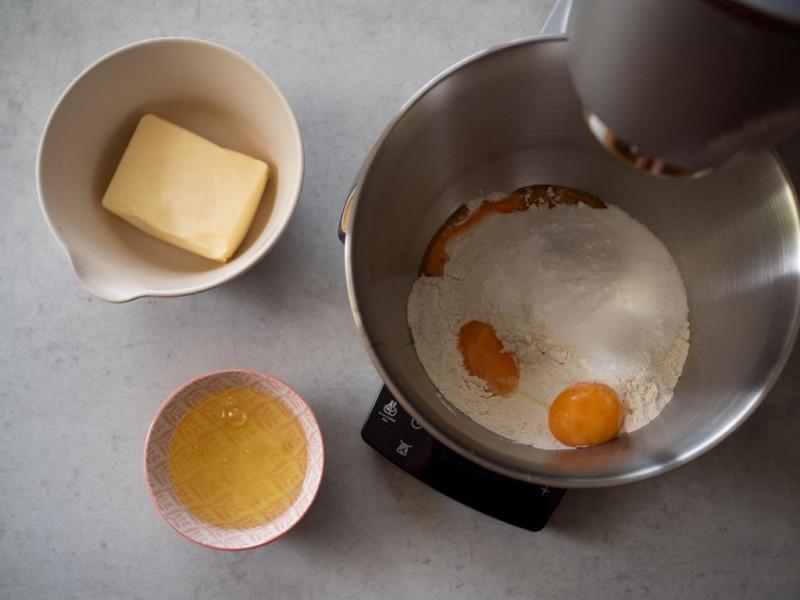 w misce mąka z cukrem i żółtkami obok masło i białka
