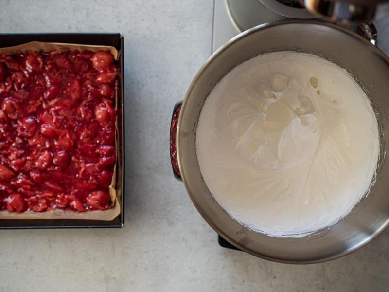 w misie robota kuchennego bosch ubita piana obok ciasto z czereśniami