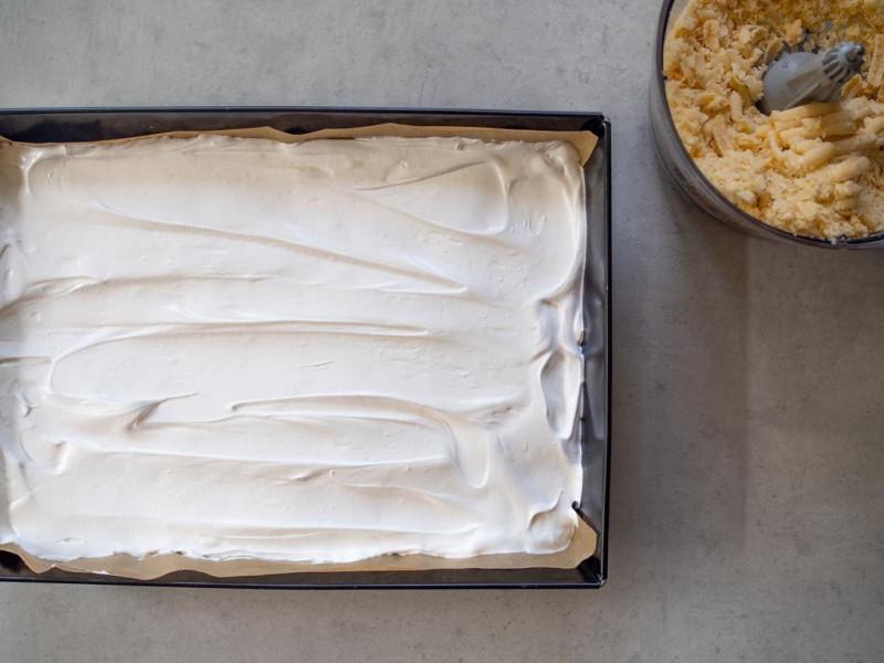 ciasto z czereśniami i bezą obok wiórki ciasta kruchego