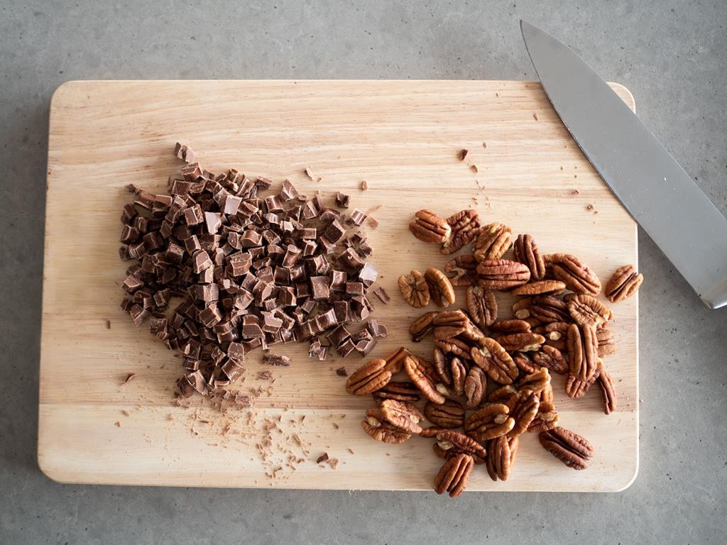 na desce pokrojona gorzka czekolada obok orzechy pekan