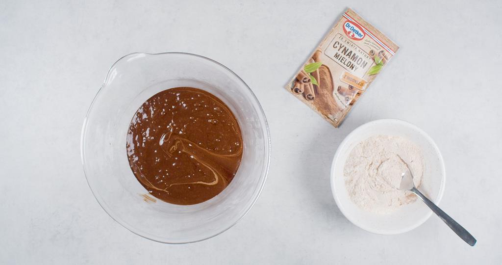 Mąką i rozpuszczona czekolada w miseczkach i cynamon Dr. Oetkera