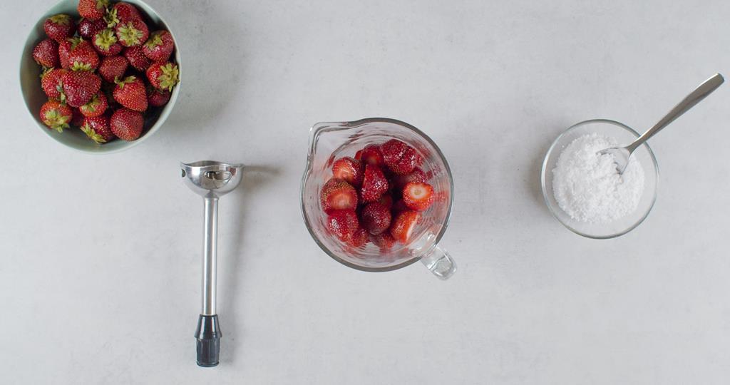 Pokrojone truskawki w wysokim naczyniu, cukier puder w miseczce