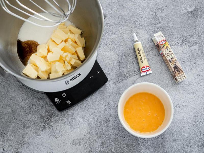 Cukier, masło i pasta z wanilii Dr. Oetker w misie robota kuchennego MUM firmy Bosch. Obok miseczka z żółtkami.